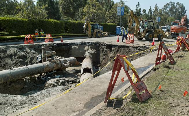 "Los Angeles Department of Water and Power crews work to repair the ""Y"" shaped juncture where a water rupture occurred near the University of California, Los Angeles, involving two main trunk lines on Sunset Boulevard, Thursday, July 31, 2014."