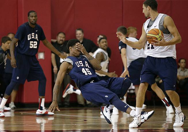 Toronto Raptors' DeMar DeRozan falls to the floor while holding his face after he was hit by Golden State Warriors' Klay Thompson during a USA Basketball minicamp scrimmage Monday, July 28, 2014, in Las Vegas.