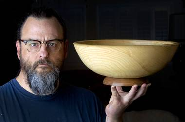 Robert Arnold of Dog House Workshop poses in his home workshop Thursday, July 31, 2014. Arnold is a craftsman who makes wooden bowls, ceramic pieces, mobiles and prints.