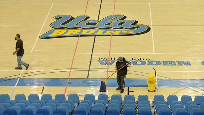 Cleaning crews work to dry the floor at UCLA's Pauley Pavilion on Wednesday, July 30, 2014, a day after a steel pipe burst along Sunset Boulevard and flooded parts of the campus and nearby streets.