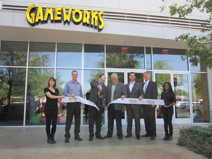 GameWorks' Chairman of the Board Howard Brand cuts the ceremonial ribbon at the grand opening of the new location as Town Square, GameWorks and city representatives look on.