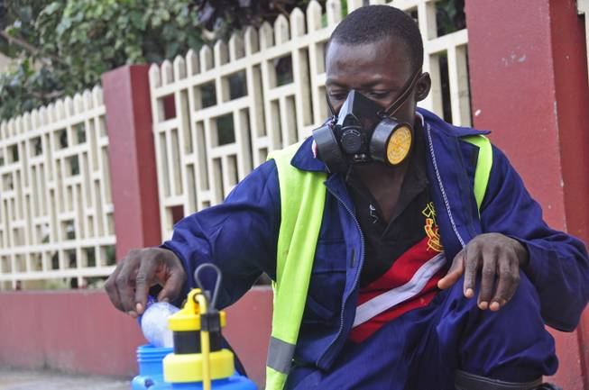 An employee of the Monrovia City Corp. mixes disinfectant before spraying it on the streets in a bid to prevent the spread of the deadly Ebola virus in the city of Monrovia, Liberia, Friday, Aug. 1, 2014.