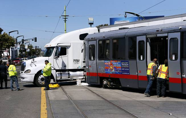 Emergency personnel arrive at the scene of a collision between a big rig truck and a MUNI light rail vehicle at the intersection of Innes and 3rd streets on Friday, Aug. 1, 2014, in San Francisco, Calif.