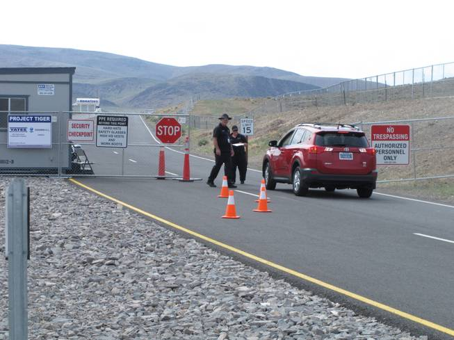"Security guards stop a car Friday Aug. 1, 2014, at the gate to the site Tahoe Reno Industrial Center about 15 miles east of Reno, where Tesla Motors has broken ground as one of the possible places to build a $5 billion ""gigafactory'' to make lithium batteries for its electric cars."
