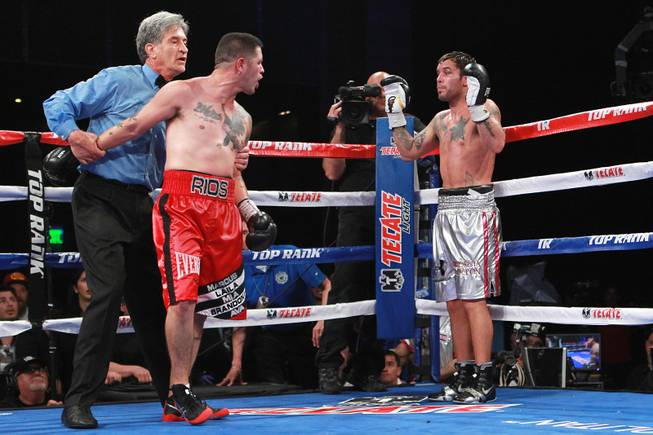 Referee Vic Drakulich holds back Brandon Rios as he goes after Diego Chaves after being separated because he was struck by a Chaves forearm to the mouth during the ninth round of their welterweight fight Saturday, Aug. 2, 2014 at the Cosmopolitan. Chaves was disqualified.