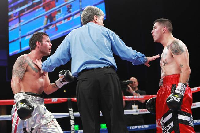 Referee Vic Drakulich separates Diego Chaves and Brandon Rios during their welterweight fight Saturday, Aug. 2, 2014 at the Cosmopolitan. Rios won after Chaves was disqualified in the ninth round.