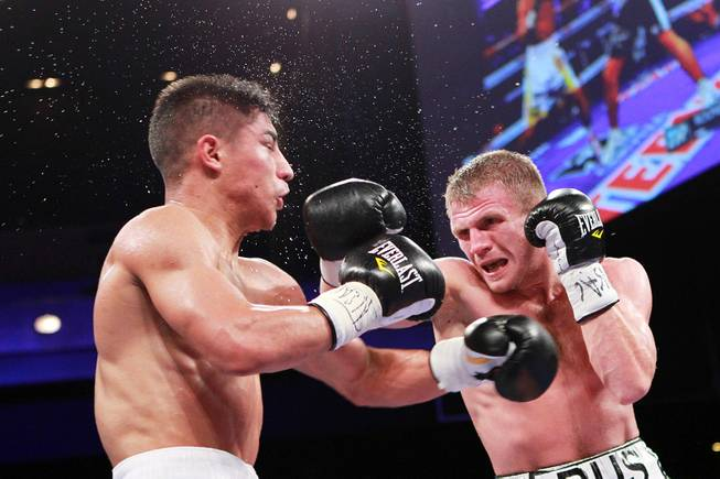 Jessie Vargas gets hit by Anton Novikov during their WBA light welterweight title fight Saturday, Aug. 2, 2014 at the Cosmopolitan. Vargas won by decision.