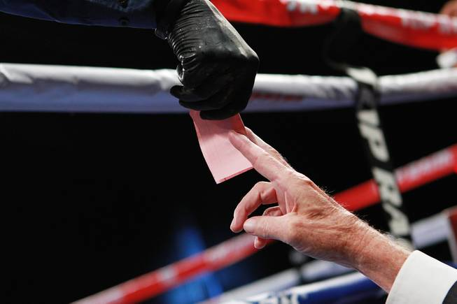 A judge hands a score sheet to referee Kenny Bayless during the Jessie Vargas vs. Anton Novikov WBA light welterweight title fight Saturday, Aug. 2, 2014 at the Cosmopolitan. Vargas won by decision.