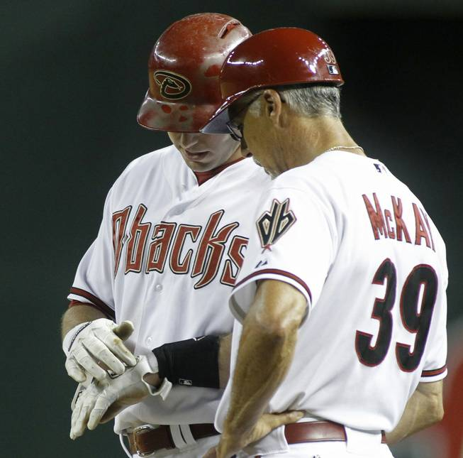 Arizona Diamondbacks' Paul Goldschmidt, left, shows first base coach Dave McKay where he was hit by a pitch during the ninth inning of a baseball game against the Pittsburgh Pirates on Friday, Aug. 1, 2014, in Phoenix. The Pirates defeated the Diamondbacks 9-4.