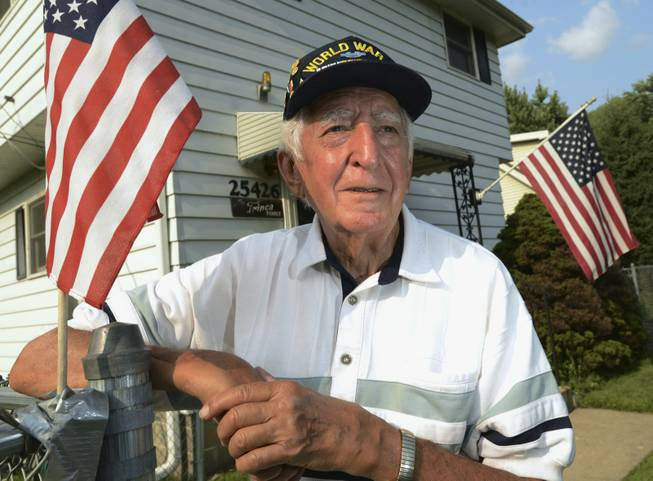 In this Thursday, July 31, 2014, photo, veteran John Trinca stands outside his home in Antioch Township, Ill. Trinca was with U.S. Army Pvt. Thomas Bateman, a soldier he had just met in the Philippines in 1945 in World War II, when Bateman was killed by Japanese machine gun fire. The Purple Heart that Bateman paid for with his life became lost and was eventually found in the 1950s by Tom McAvoy as a kid in Chicago. Trinca will be on hand Sunday, Aug. 3, 2014, when the Purple Heart will be returned to Bateman's family in Grayslake, Ill.