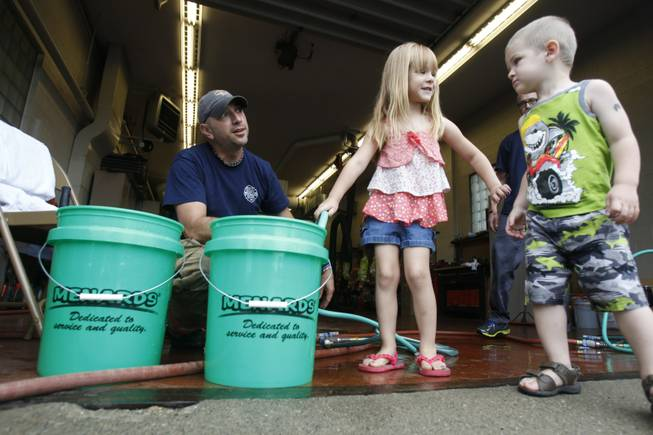 Firefighter Bryan West, left, works with Clara Cousino, 4, center, and Clay Cousino, 2, right, to fill buckets with water at the fire station in Oregon, Ohio, on Saturday, Aug. 2, 2014. Ohio's governor is declaring a state of emergency in northwest Ohio, where about 400,000 people are being warned not to drink the water.