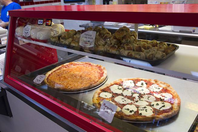 Pizza, garlic knots and fresh homemade Mozzarella cheese is shown in a display case at Cugino's Italian Deli and Pizzeria Sunday, Aug. 3, 2014.