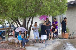 Neighbors watch as Metro Police investigate an officer-involved-shooting near Pecos and Alexander roads August 3 , 2014.