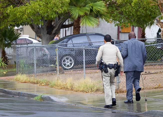 A Metro Police officer escorts a man to his home at the scene of an officer-involved-shooting near Pecos and Alexander roads August 3 , 2014.