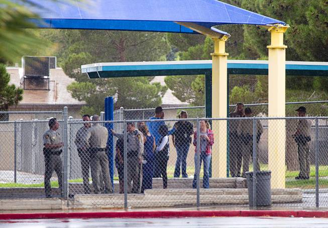 Metro Police officers take advantage of a covered playground at Cox Elementary School by the scene of an officer-involved-shooting near Pecos and Alexander roads August 3 , 2014.