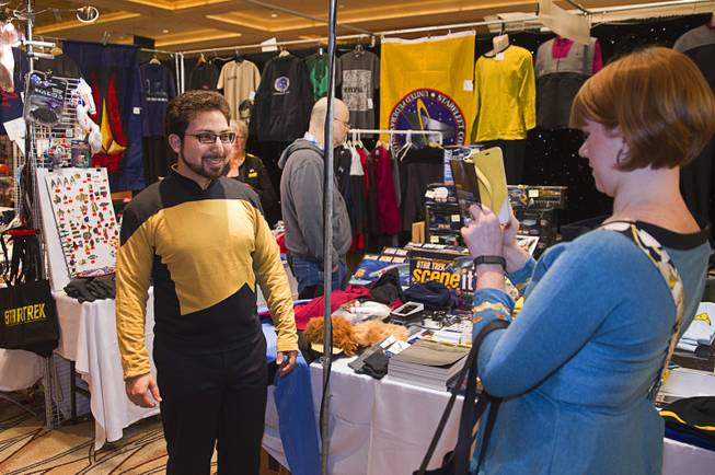 Ken Rosenberg of Bloomington, Ind. has his photo taken by his wife as he tries on a Star Trek: The Next Generation uniform during the final day of the 13th annual Official Star Trek Convention at the Rio Sunday, Aug. 3, 2014.