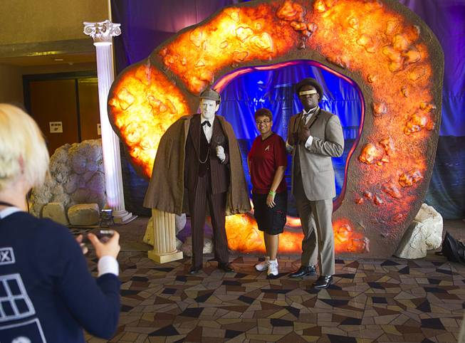 "Simone Boyer, center, of New York City poses with Eric Hall, left, and Darrell Mashia in front of the ""Guardian of Forever"" during the final day of the 13th annual Official Star Trek Convention at the Rio Sunday, Aug. 3, 2014. Hall and Mashia are dressed as Lieutenant Commander Data and Lieutenant Commander Geordi La Forge respectively."