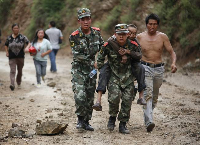 In this photo released by China's Xinhua News Agency, rescuers transport injured people after an earthquake in Zhaotong City in the densely populated Ludian county in southwest China's Yunnan Province, Sunday Aug. 3, 2014. The strong earthquake in southern China's Yunnan province toppled thousands of homes on Sunday, killing at least 175 people and injuring more than 1,400, according to China's official Xinhua News Agency.