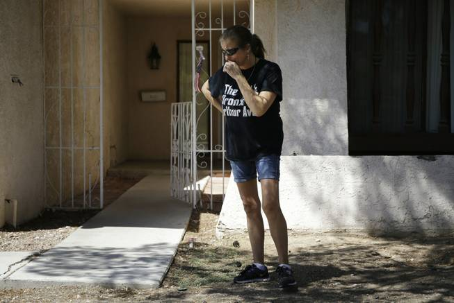 Julie Ramos cries while standing in front of her home Wednesday, July 30, 2014, in Las Vegas. Ramos was injured and her husband Richard Ramos was killed in a home invasion Tuesday.