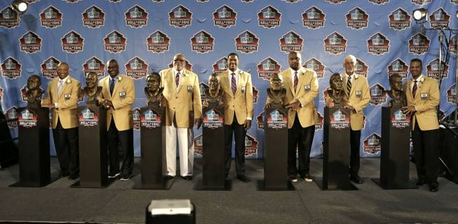 Inductees Aeneas Williams, Derrick Brooks, Claude Humphrey, Michael Strahan, Walter Jones, Ray Guy and Andre Reed, from left, pose with their busts at the Pro Football Hall of Fame enshrinement ceremony Saturday, Aug. 2, 2014, in Canton, Ohio.