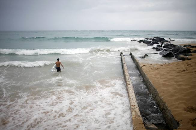 A surfer enters the water to take advantage of the high waves in San Juan, Puerto Rico, on Saturday, Aug. 2, 2014. Bertha pushed just south of Puerto Rico on Saturday as it unleashed heavy rains and strong winds across the region.