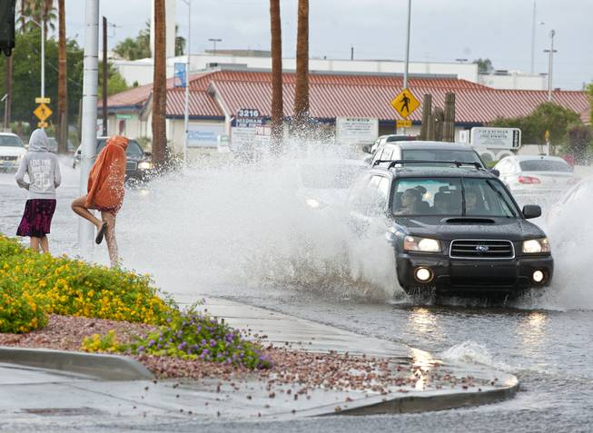 A pedestrian attempts to lean away from the wake of a passing car after an afternoon downpour temporarily turned Charleston Boulevard into a rushing river on Monday afternoon.