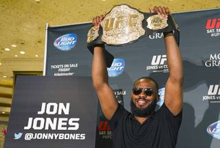UFC light heavyweight champion Jon Jones holds up his belt during a UFC press conference at the MGM Grand Monday Aug. 4, 2014.
