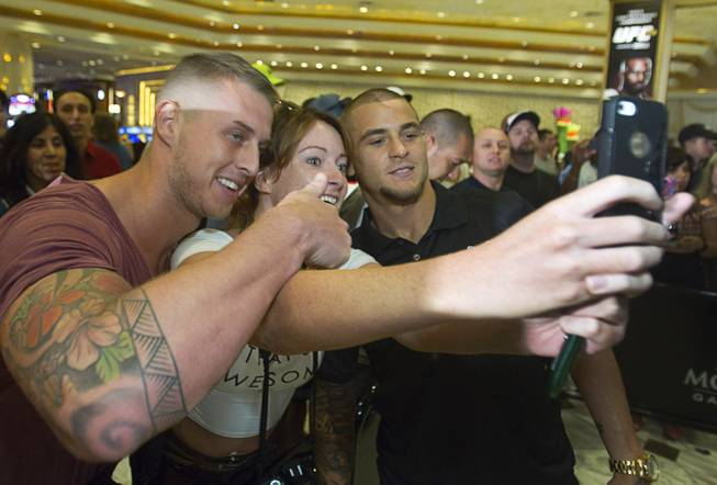 UFC featherweight fighter Dustin Poirier, right, poses with fans Lewis and Joanne Standring of Manchester, England during a UFC press conference at the MGM Grand Monday Aug. 4, 2014.