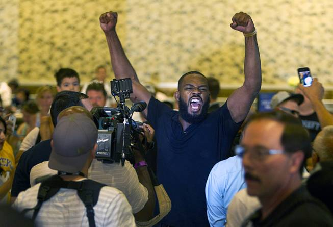 UFC light heavyweight champion Jon Jones is triumphant as he leaves the MGM lobby after getting into a fight with challenger Daniel Cormier during a UFC press conference at the MGM Grand Monday Aug. 4, 2014.