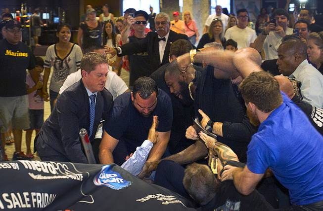 MGM Grand security try to to separate UFC light heavyweight champion Jon Jones (top) and challenger Daniel Cormier after the two started fighting during a UFC press conference at the MGM Grand Monday Aug. 4, 2014.