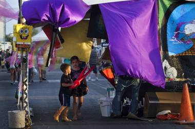 Kids make their way through an art vendor's space with colorful cloth at First Friday activities on Friday, August 1, 2014.
