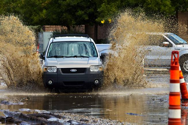 A car is driven quickly through deep water collecting due to recent heavy rains along West Grand Teton Drive at the intersection of North Tenaya Way on Monday, August 4, 2014.