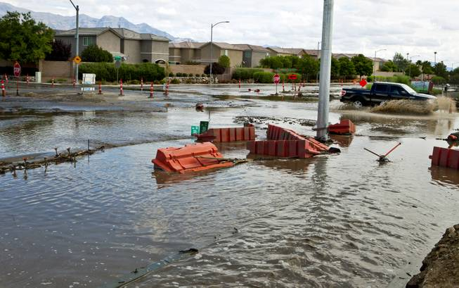 A truck is driven quickly through deep water collecting due to recent heavy rains along West Grand Teton Drive at the intersection of North Tenaya Way on Monday, August 4, 2014.