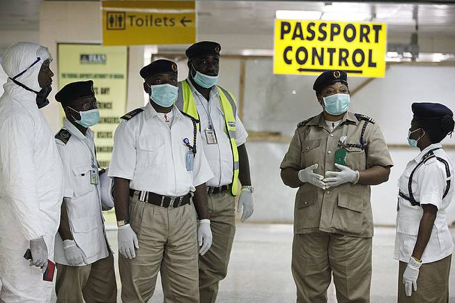 Nigeria health officials wait to screen passengers at the arrival hall of Murtala Muhammed International Airport in Lagos, Nigeria, Monday, Aug. 4, 2014. Nigerian authorities on Monday confirmed a second case of Ebola in Africa's most populous country, an alarming setback as officials across the region battle to stop the spread of a disease that has killed more than 700 people.