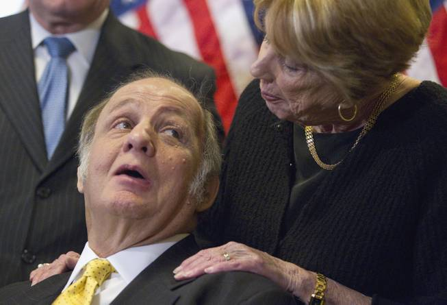 This March 30, 2011, file photo shows former White House press secretary James Brady, left, who was left paralyzed in the Reagan assassination attempt, looking at his wife, Sarah Brady, during a news conference on Capitol Hill in Washington marking the 30th anniversary of the shooting. A Brady family spokeswoman says Brady has died at 73.