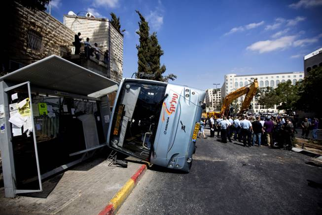A damaged bus flipped over after attack in Jerusalem, Monday, Aug. 4, 2014. An Israeli-declared cease-fire and troop withdrawals slowed violence in the Gaza war Monday, though an attack on Israeli bus that killed one person in Jerusalem underscored the tensions still simmering in the region.