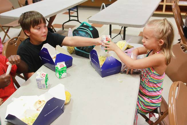 Aidan Beshara hands a carton of milk to his sister LillyMay Beshara during a summer day camp at the Stupak Community Center Tuesday, Aug. 5, 2014.