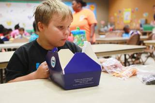 Keaton Beshara eats his lunch during a summer day camp at the Stupak Community Center Tuesday, Aug. 5, 2014.