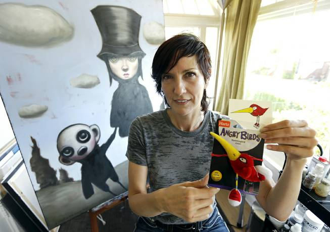 "Artist Juli Adams on Tuesday, Aug. 5, 2014, in her home art studio in Seattle with one of her original drawings that a line of plush pet toys called ""Angry Birds"" was based."