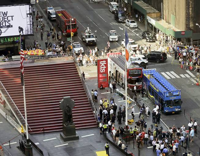 Two double-decker tour buses sit at 47th Street and 7th Avenue in Times Square after colliding Tuesday, Aug. 5, 2014, in New York.