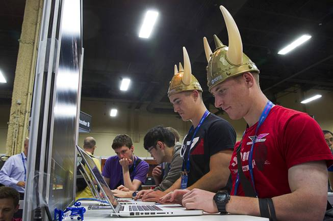 "K.C. McGaffey, center, and John Dimmer, right, compete in the ""Hacker Kombat"" challenge at the WhiteHat Security booth during the Black Hat USA 2014 hacker conference at the Mandalay Bay Convention Center Aug. 6, 2014."