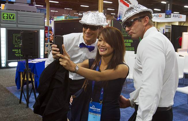 Quan Ngo, center, an information technology research analyst from Canada, takes a selfie with Rocky Fain, left, and John Cook at the Securonix booth during the Black Hat USA 2014 hacker conference at the Mandalay Bay Convention Center Aug. 6, 2014.
