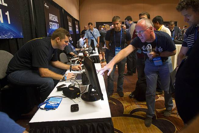 Glenn Wilkenson, left, of SensPost, an information security company, demonstrates a technique for collecting unique, identifiable information from mobile devices during the Black Hat USA 2014 hacker conference at the Mandalay Bay Convention Center Aug. 6, 2014.