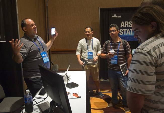 David Schwartzberg, left, a senior sales engineer at MobileIron, demonstrates the ZitMo Non web App prototype during the Black Hat USA 2014 hacker conference at the Mandalay Bay Convention Center Aug. 6, 2014. The App detects the Zitmo malware on Android devices. The malware can be used to steal numbers used in mobile financial transactions, Schwartzberg said.