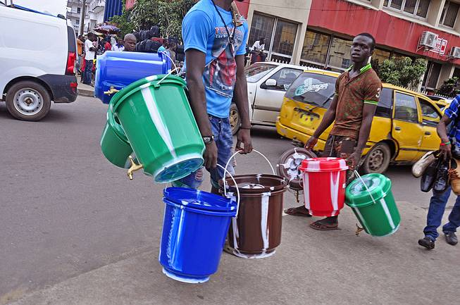 Water bucket sellers hawk their wares as the public buy them to try to protect them selves from the deadly Ebola virus in Monrovia, Liberia, Wednesday, Aug. 6, 2014. The price of buckets has increased as Liberian people are encouraged to wash their hands after filling it with disinfectant to prevent the spread of the deadly Ebola virus.