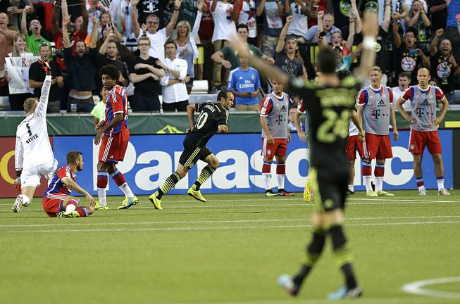 Los Angeles Galaxy forward Landon Donovan, center rear, celebrates after he scored the go-ahead goal on Bayern Munich goalkeeper Manuel Neuer, left, in the second half of the MLS All-Star soccer game, Wednesday, Aug. 6, 2014, in Portland, Ore. The MLS All-Stars won 2-1.