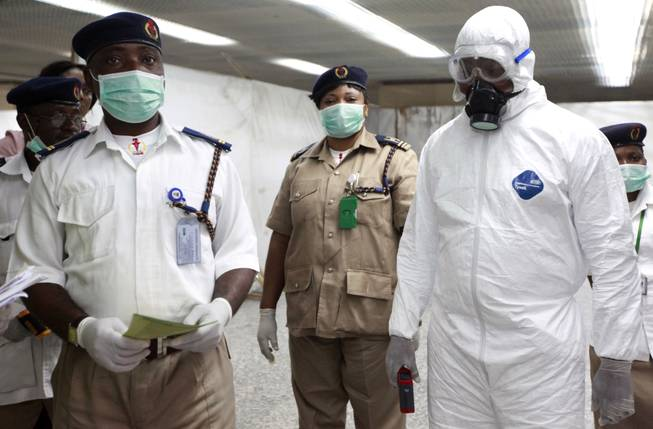 Nigerian health officials wait to screen passengers for Ebola at the arrivals hall of Murtala Muhammed International Airport in Lagos, Nigeria, Monday, Aug. 4, 2014.