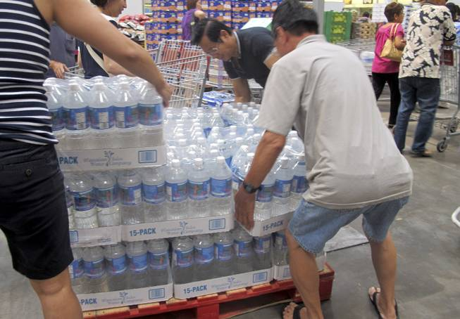 Shoppers lift cases of bottled water in preparation for a hurricane and tropical storm heading toward Hawaii at the Iwilei Costco in Honolulu on Tuesday, Aug. 5, 2014.