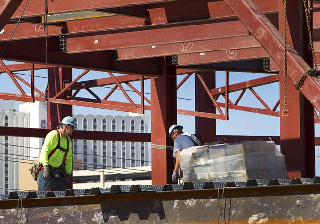 Iron workers are shown during construction of a building at the northeast corner of Sahara Avenue and Las Vegas Boulevard South Thursday, August 7, 2014. A Walgreens will occupy about half of the first floor. Wilger Enterprises is the general contractor on the project.
