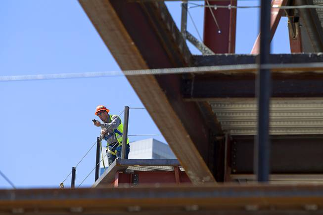 A construction worker makes a call from a building at the northeast corner of Sahara Avenue and Las Vegas Boulevard South Thursday, August 7, 2014. A Walgreens will occupy about half of the first floor. Wilger Enterprises is the general contractor on the project.